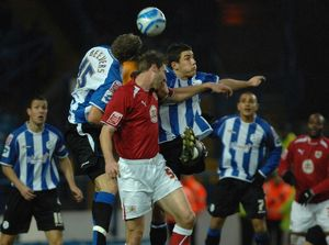 Jamie McCombe jumps to compete with the sheffield wednesday defence