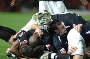Lee Johnsons team mates pile on top to join the celebrations